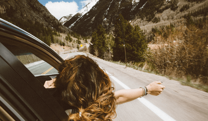 Girl hanging out of car window while driving in mountains